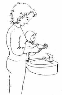 Eine Mutter hält ihr Neugeborenes über ein Waschbecken zum Pieschern ab